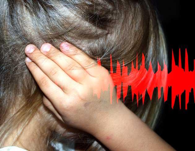 Une fille qui a mal au oreilles car gêné par le bruit.
