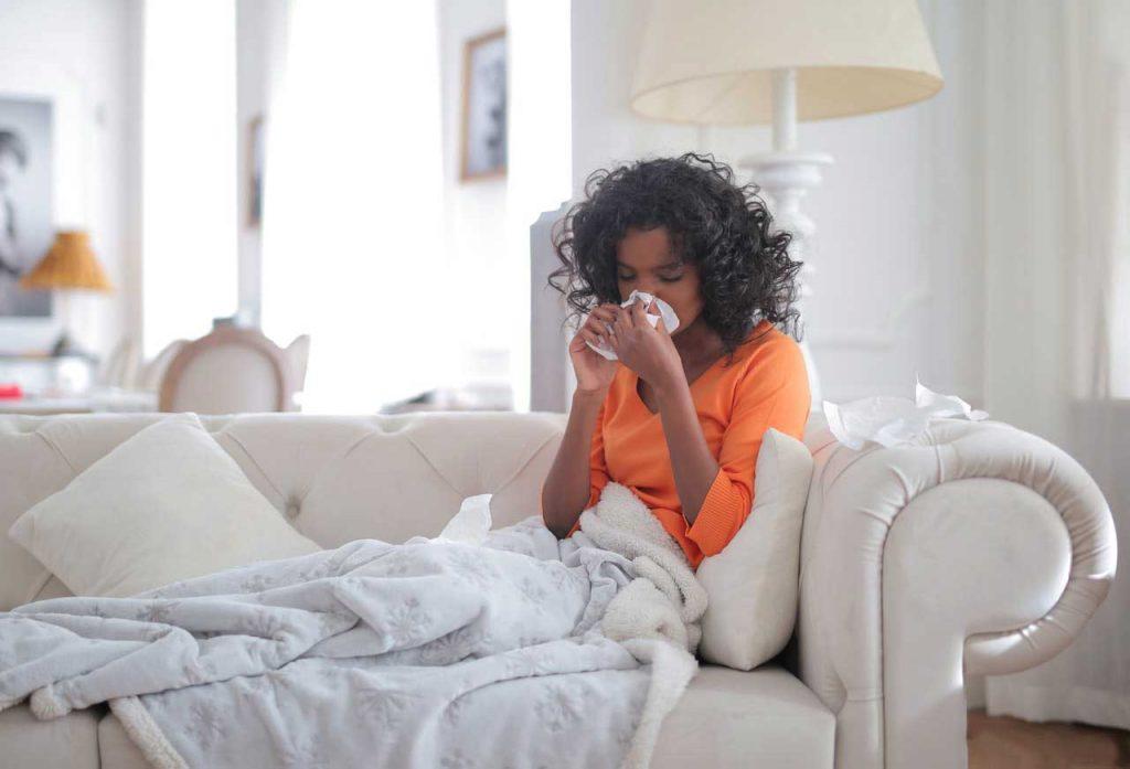 Une femme allongé sur un canapé qui est touché par un rhume des foins