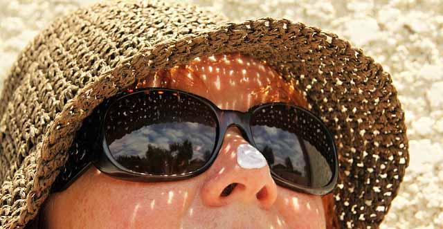 une femme avec de la crème solaire sur le nez