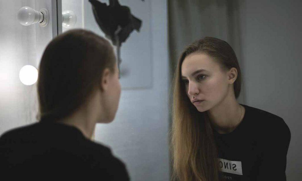 une femme qui regarde son visage dans le miroir